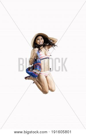 Young woman leaping while wearing straw hat and bikini isolated on white background