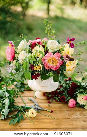 arts and crafts, wedding, decor, celebration, summer, nature concept - bunch of ornamental flowers like peonies, roses, avalanches and diathuses, decorated with verdure, placed in vase on wooden table