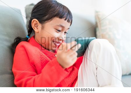Little girl looking at mobile phone at home