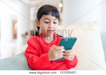 Little girl play cellphone at home
