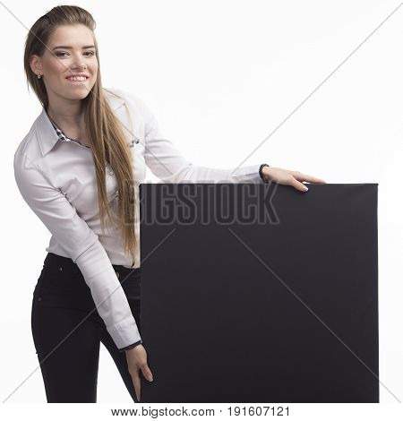 Young happy woman portrait of a confident businesswoman showing presentation, pointing paper placard gray background. Ideal for banners, registration forms, presentation, landings, presenting concept..
