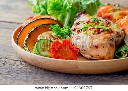 Homemade chicken breast barbecue on wood plate served with grilled vegetables. Delicious chicken barbecue and grilled vegetables for lunch or dinner. Roast chicken breast on rustic wood table. Chicken barbecue. Pork steak.