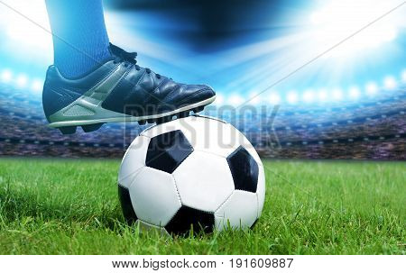 Feet of soccer player with ball on football field.