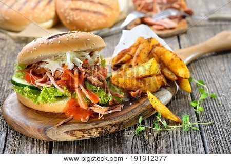 Barbecue pulled pork sandwich with coleslaw, hot BBQ sauce and potato wedges in a paper bag served on a wooden table