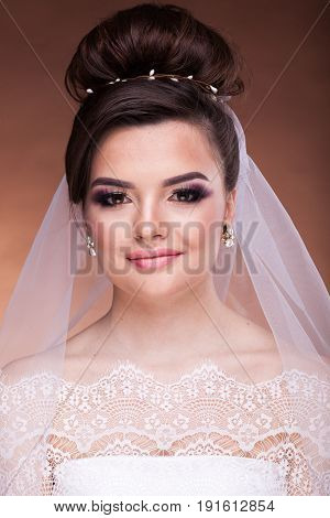 Close up of bride with professional hairstyle and make up on brown background in studio photo. Bridal make up and hairstyle. Fashion and elegance