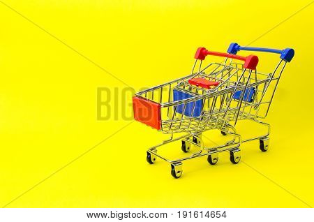 mini red and blue color supermarket shopping cart on yellow background holiday sale and online shopping concept selective focus copy space