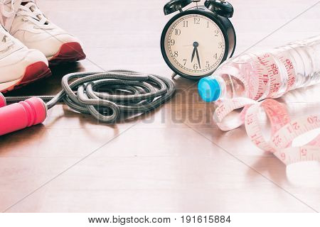 Sport equipments and bottle of water with measuring-tape Workout and Healthy lifestyle