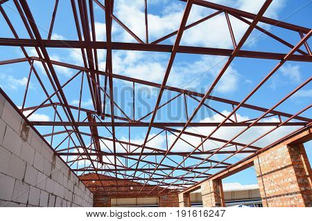 Steel roof trusses details with clouds sky background. Roofing Construction. Steel roof trusses sitting on concrete pole view from inside