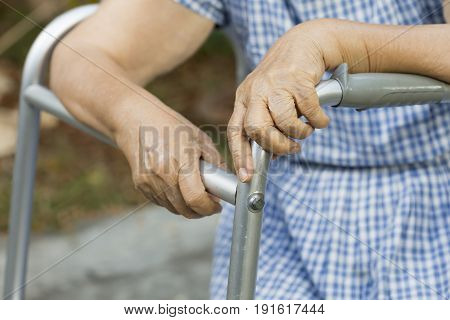 Elderly sitting in backyard with walker at home