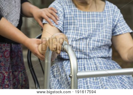 senior woman sitting use a walker with caregiver.