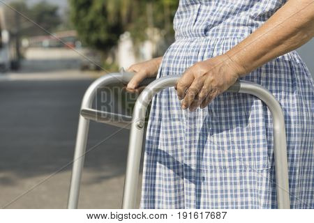 senior woman using a walker cross street.
