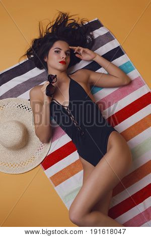 Fashion photo of beautiful and young lady in swimsuits posing in studio, is resting on a colorful towel