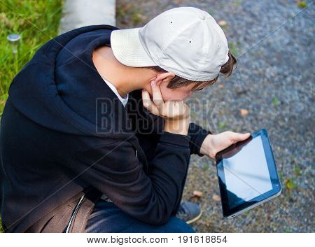 The Teenager with Tablet Computer sit outdoor