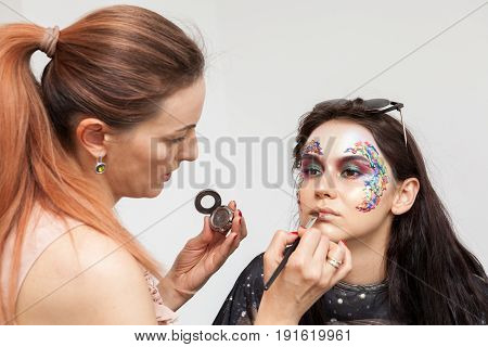 Make-up artist applying colors on a creative make up. Beauty and fashion. Creativity and makeup. Cosmetics and backstage preparation for photo shooting