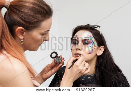 Artist applying colors on a creative make up. Beauty and fashion. Creativity and makeup. Cosmetics and backstage preparation for photo shooting
