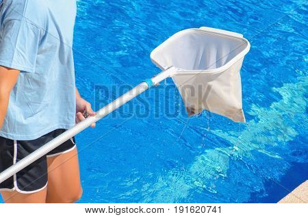 Detail on the hands of a man cleaning the swimming pool with a net. Summer pool maintenance service