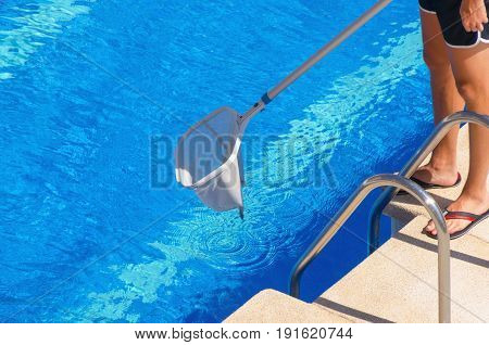 Am An Cleaning The Swimming Pool With A Net In The Poolside