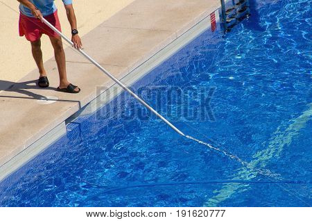 Guy Cleaning The Swimming Pool With A Brush From The Poolside