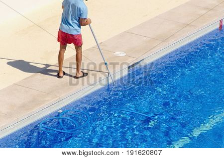 Guy Cleaning The Swimming Pool With A Brush