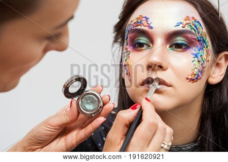 Make-up artist working with colors on model face. Beauty and fashion. Creativity and makeup. Cosmetics and backstage preparation for photo shooting