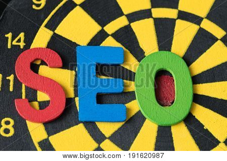 SEO Search engine optimization concept as colorful alphabets abbreviation SEO on dartboard.