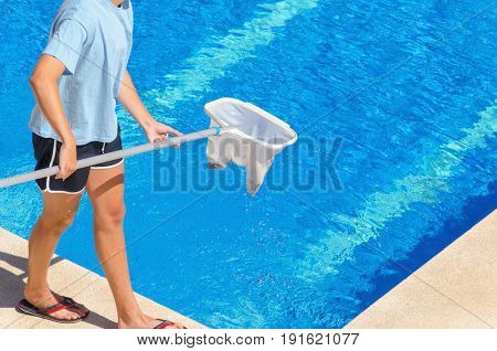 Young Man Cleaning The Swimming Pool With A White Plastic Net