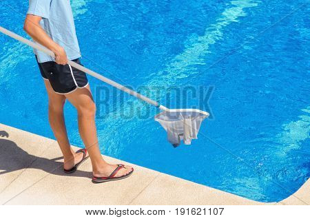 Young Man Wearing Shorts Cleans The Swimming Pool With A White Net