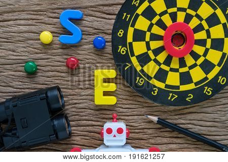 SEO search engine optimization concept with pencil dartboard magnifying glass robot and alphabets abbreviation SEO on wood table.