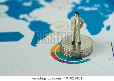 financial business concept as miniature businessman standing on stack of coins at the center of analysis infographic pie chart paper.