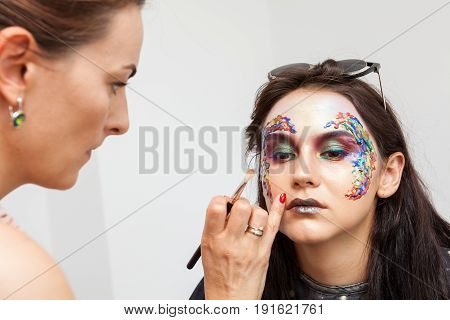 Make-up artist applying makeup on beautiful model. Beauty and fashion. Creativity and makeup. Cosmetics and backstage preparation for photo shooting