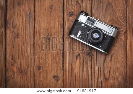 Old camera on an old wooden background. view from above.