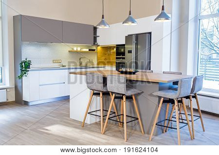Modern kitchen design in light interior. There is also a kitchen island in the room. Kitchen and living room combined.
