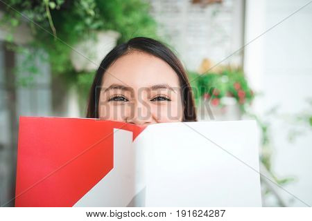 Portrait Of Young Asian Woman Reading Book At Home