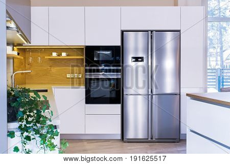 Modern home interior. Modern kitchen design in light interior. There is also a kitchen island in the room. Kitchen and living room combined. European furniture, design, technologies. Front view.