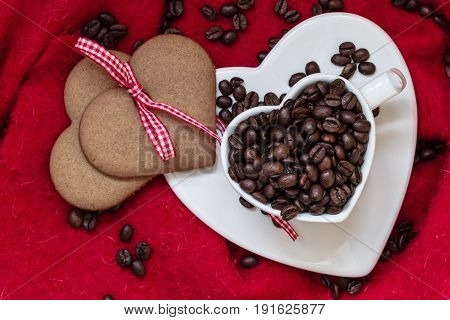 Coffee love concept. Coffee beans in heart shaped white cup and sweet cookie gingerbread with ribbon on red cloth background. Top view