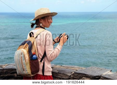 Pretty girl tourist taking pictures on the beach