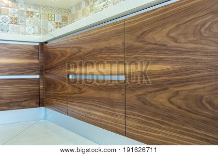 Modern home interior. Texture of the wood of the facades of the modern kitchen are made from walnut veneer.