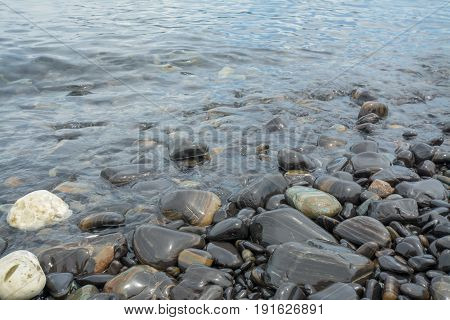 Black stones beach as a background black stones coast with silky waves from long exposure at Lipe island in Thailand.