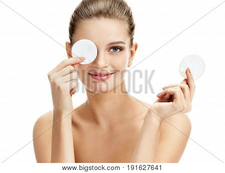 Funny beautiful model holding cotton pads up to her eyes. Portrait of blonde girl on white background. Youth and skin care concept