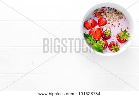 Huge bowl of granola with strawberries and mint leaves, additional textspace left on side, topview