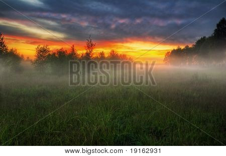 Misty sunset in the field. It is photographed in Russia. 60 kilometers from Moscow. The end of summer.