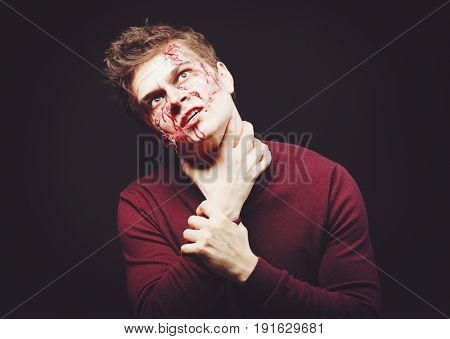 Young man with Halloween makeup on dark background