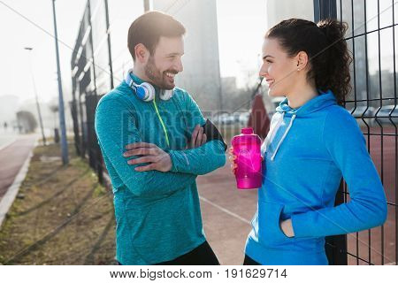 Happy sportsman and sportswoman flirting outdoor after fitness exercising