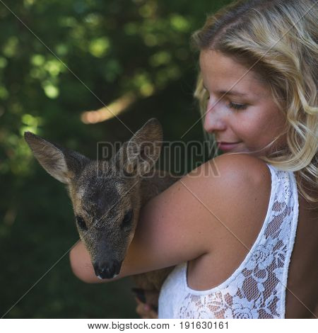 Beautiful woman in the forest with roe deer fawn. Animal protection concept.