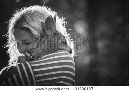 Young beautiful woman hugging animal roe deer fawn in the sunshine, protecting an animal