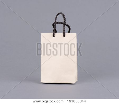 Empty Shopping Bag from craft paper, Recycled paper shopping bag on gray background. Photo