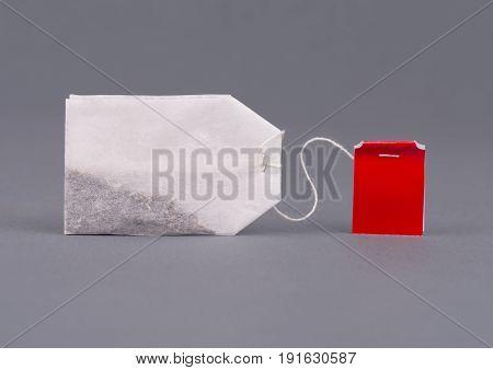 Close-up tea bag on grey background mock up. Teabag with red label