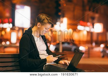 Young male freelancer working in city street in night time, blurred lights background, free space. Smiling guy reading message on smartphone, while he working on laptop outside.