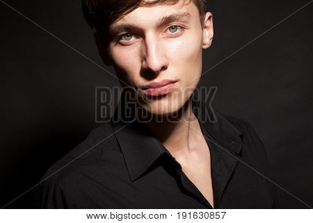 Portrait of beautiful male model on black background in studio photo. Expression and style