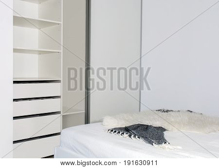 Modern home interior.Built-in wardrobe with sliding doors in the light interior of the bedroom. Small room. One of the doors of the built-in wardrobe is open. European furniture, design, technologies.